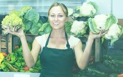 Vendedor de sexo femenino joven amistoso que sostiene la col fresca en mercado Imagen de archivo libre de regalías