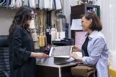 Vendedor de sexo femenino que muestra las telas para las muestras de alfombras Imagen de archivo