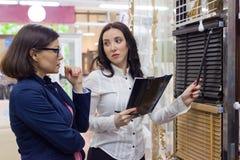 Vendedor de sexo femenino que muestra las telas para las muestras de persiana Foto de archivo