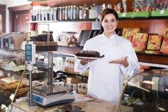 Vendedor de sexo femenino que ofrece la torta de chocolate festiva fotos de archivo libres de regalías