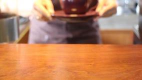 Vendedor de sexo femenino que sirve la taza de café caliente almacen de video