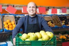 Vendedor de sexo masculino bondadoso que vende manzanas en el colmado Foto de archivo libre de regalías