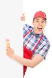 Vendedor de sexo masculino emocionado del helado que presenta detrás de un panel Foto de archivo libre de regalías