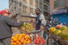 Vendedor de sexo masculino de la fruta en el centro histórico de Katmandu imagenes de archivo
