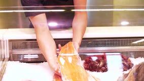 Vendedor de sexo masculino que pone el prendedero de pescados al refrigerador en la tienda metrajes