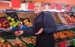 Vendedor de sexo masculino que vende manzanas en el colmado Fotografía de archivo libre de regalías