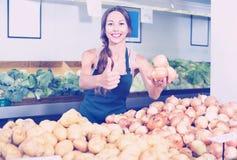 Vendedor de sorriso da jovem mulher que mostra cebolas amarelas foto de stock royalty free