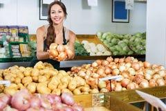 Vendedor de sorriso da jovem mulher que mostra cebolas amarelas imagens de stock