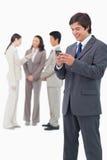 Vendedor de sorriso que guardara o telemóvel com a equipe atrás dele Fotos de Stock Royalty Free