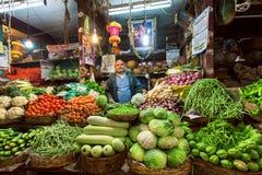Vendedor del calabacín, de la col, de los verdes y de otras verduras esperando a clientes en el mercado del granjero Fotografía de archivo libre de regalías