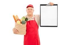 Vendedor del mercado que sostiene un tablero Imagen de archivo libre de regalías