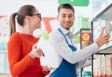 Vendedor del supermercado que ayuda a un cliente foto de archivo libre de regalías