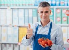 Vendedor del supermercado que sostiene los tomates imagen de archivo libre de regalías