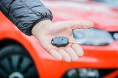 Vendedor do automóvel - homens que guardam a chave do carro na frente do carro moderno vermelho fotografia de stock royalty free