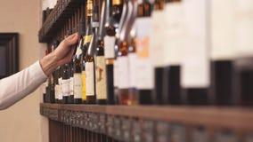 Vendedor elegante del vino que selecciona el vino para los clientes en tienda de vino almacen de metraje de vídeo