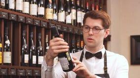 Vendedor elegante del vino que sostiene una botella de vino y que lee la etiqueta en una bodega almacen de metraje de vídeo