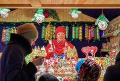 Vendedor en la parada con los caramelos coloridos en el mercado de la Navidad de Vilna Fotos de archivo libres de regalías