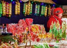 Vendedor en la parada con los caramelos coloridos en el mercado Vilna de la Navidad Fotos de archivo libres de regalías