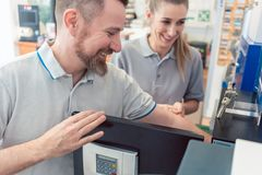 Vendedor en su tienda con la venta de cliente una caja fuerte fotografía de archivo
