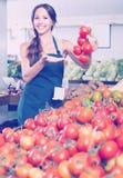Vendedor fêmea contente que guarda tomates maduros frescos Fotos de Stock Royalty Free