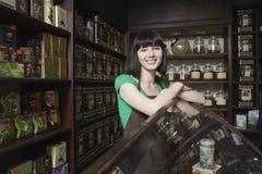 Vendedor fêmea do chá que inclina-se no armário de exposição Fotos de Stock
