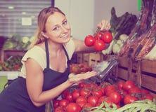 Vendedor fêmea novo contente que guarda tomates maduros frescos no mercado Foto de Stock