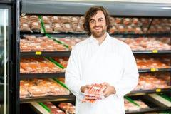 Vendedor feliz Holding Meat Packages no contador imagem de stock
