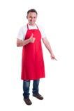 Vendedor feliz que señala abajo y que muestra el pulgar para arriba Foto de archivo libre de regalías