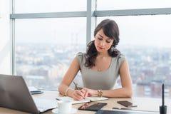 Vendedor femenino joven que se sienta en la oficina moderna que hace notas en su libreta Empleado que trabaja en la tabla de trab Foto de archivo libre de regalías