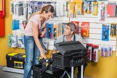 Vendedor Guiding Customer In que seleciona ferramentas em Fotografia de Stock Royalty Free