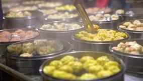 vendedor 4K que vende la bola de masa hervida y Shaomai en el mercado asiático de la comida de la calle de Taiwán almacen de video