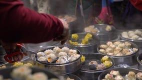 vendedor 4K que vende la bola de masa hervida y Shaomai en el mercado asiático de la comida de la calle de Taiwán metrajes