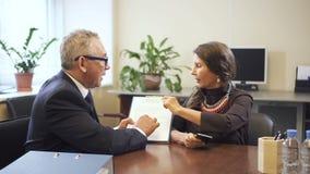 Vendedor maduro y mujer mayor que discuten el contrato de la hipoteca en oficina de la agencia inmobiliaria real almacen de metraje de vídeo