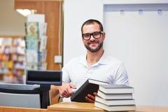 Vendedor na verificação geral em uma livraria Fotos de Stock