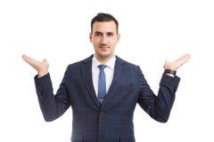 Vendedor o agente inmobiliario joven que presenta dos opciones con imagen de archivo libre de regalías