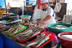 Vendedor peruano de sexo femenino en un mercado de los mariscos de los pescados imagen de archivo