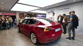 Vendedor que apresenta o carro vermelho do Tesla Model 3 elétricos novos filme