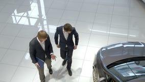 Vendedor que ayuda al cliente en la sala de exposición del coche almacen de metraje de vídeo