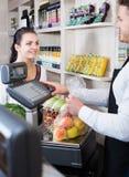 Vendedor que ayuda al cliente para pesar compras Foto de archivo