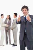 Vendedor que dá os polegares acima com a equipe atrás dele Fotografia de Stock Royalty Free