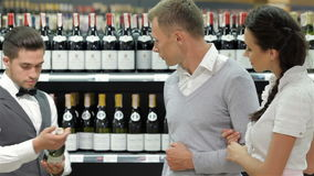 Vendedor que da consejo sobre la botella de compra de vino metrajes