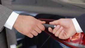 Vendedor que da la llave del nuevo coche almacen de metraje de vídeo