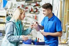 Vendedor que demuestra el rodillo de pintura al comprador Imágenes de archivo libres de regalías
