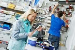 Vendedor que demuestra el rodillo de pintura al comprador Fotos de archivo libres de regalías