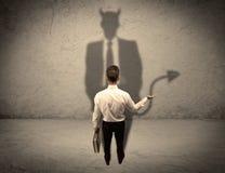 Vendedor que enfrenta sua própria sombra do diabo imagem de stock royalty free
