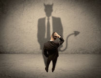 Vendedor que enfrenta sua própria sombra do diabo Fotos de Stock