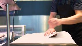 Vendedor que envuelve pescados en el papel en la tienda de los mariscos metrajes