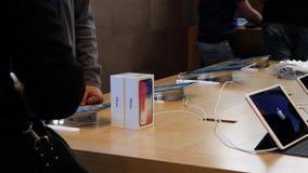 Vendedor que explora el iphone X antes de venta almacen de video