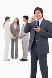 Vendedor que fala no telemóvel com a equipe atrás dele Fotografia de Stock