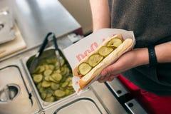 Vendedor que faz o hotdog no snack bar do fast food fotos de stock